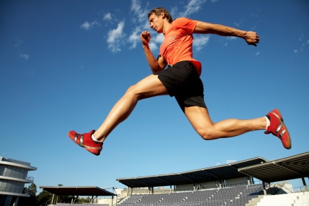 hombre deportista: joven atleta muscular se ejecuta en el fondo del estadio de cielo azul
