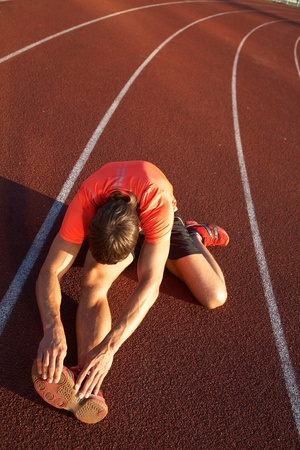 beine spreizen: junge Athlet sitzt auf dem Laufband Stadion gespreizten Beinen.