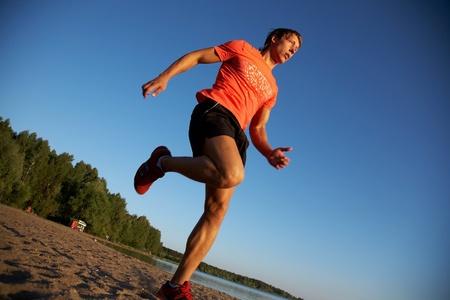 men running: Young man running along the seashore at sunset. Stock Photo