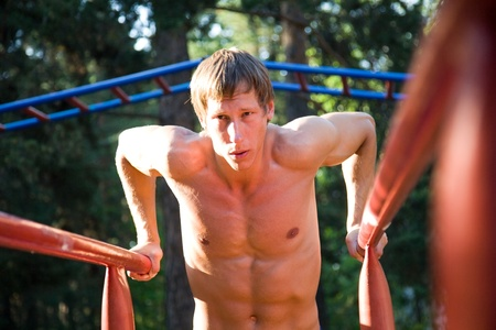 young handsome man performs sport exercises to strengthen muscles outdoors photo
