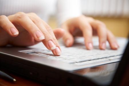 net surfing: Mani femminili digitando su un computer portatile
