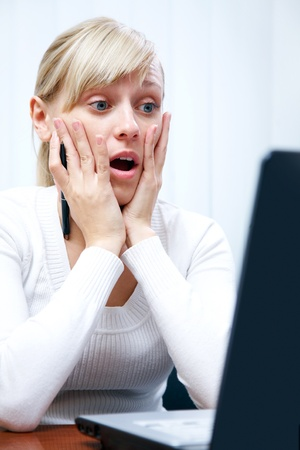emotion faces: young white woman was surprised at work at the computer Stock Photo