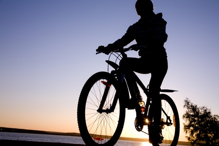 silhouette of cyclist in motion on the background of beautiful sunset photo