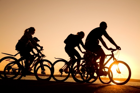 Image of sporty company  friends on bicycles outdoors against sunset. Silhouette photo