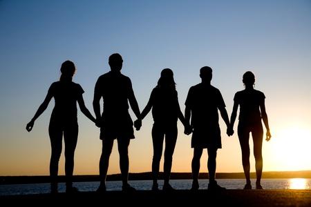 młodzież: grupa szczęśliwych młodych ludzi patrzy na piękny zachód słońca latem na plaży Zdjęcie Seryjne