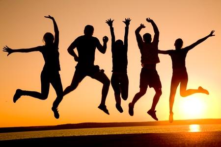 gente bailando: Grupo de jóvenes felices bailando en la playa en el atardecer de verano hermosa