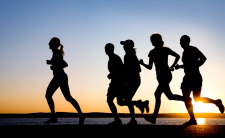 people jogging: grupo de j�venes que se ejecuta en la playa en la puesta de sol hermosa Foto de archivo