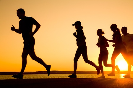 group of young people runs at the beach on beautiful summer sunset  photo