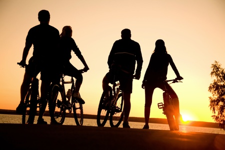 Image of sporty company  friends on bicycles outdoors against sunset. Silhouette. Stock Photo - 10571982