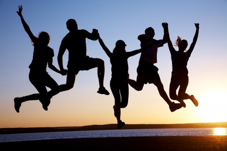 happy people jumping: group of happy young people jumping at the beach on beautiful summer sunset