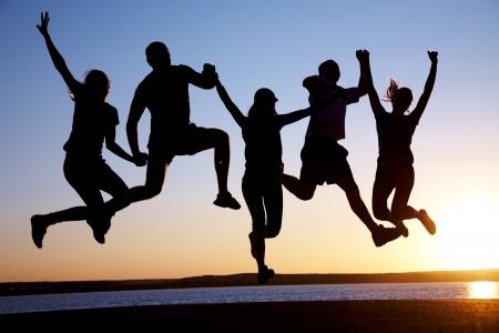 gente saltando: Grupo de jóvenes felices saltando en la playa en el atardecer de verano hermosa