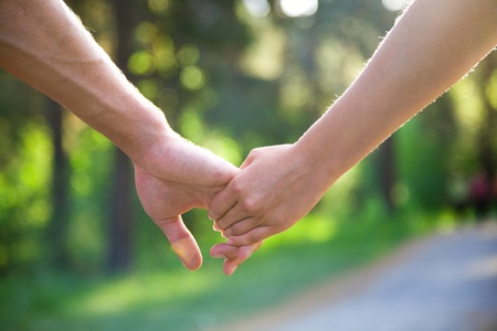 a marriage meeting: two pairs of hands in love tenderly hold together Stock Photo