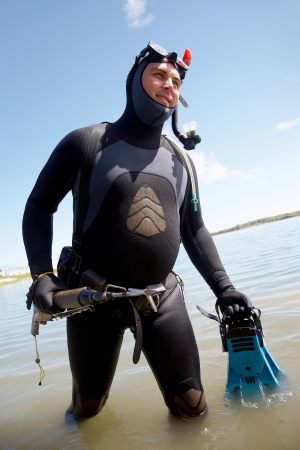 underwater hunter in full  equipment out of the water with  smile photo