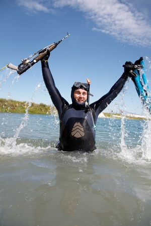 deep sea diver: underwater hunter  in full  equipment  out of the water rejoicing emotional victory