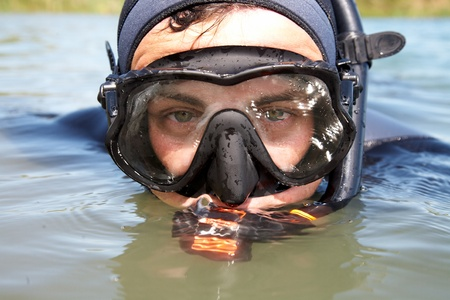 portrait of  diver in  diving suit and  mask looking out of the water. Close-up photo