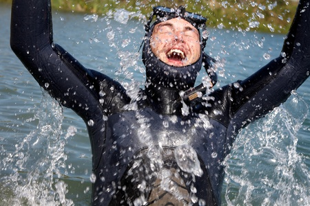 sky dive: diver in  diving suit with splashes of jumping out of  water and gasping for air
