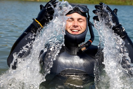 diver in  diving suit with splashes of jumping out of  water and gasping for air photo