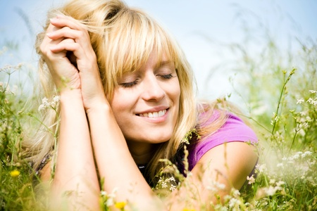 young beautiful woman with fair hair lying and  enjoy on the meadow photo