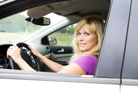 Portrait of young beautiful woman with fair hair sitting in the car  photo