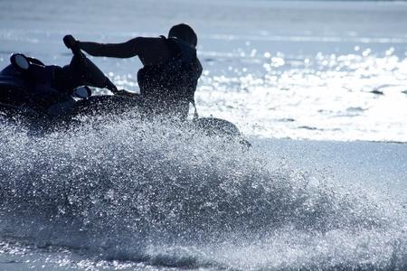jet skier: strong man drive on the jetski above the water at sunset .silluet. spray.