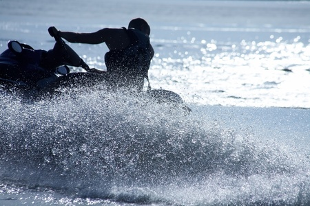 moto acuatica: unidad de hombre fuerte en el jetski por encima del agua al atardecer .silluet. aerosol. Foto de archivo