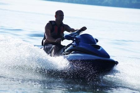 moto acuatica: unidad de hombre fuerte en la jetski por encima del agua en .silluet del atardecer. aerosol.