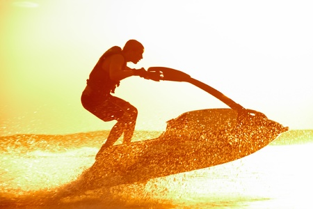 jetski: strong man drive on the jetski above the water at sunset .silhouette. spray. Stock Photo
