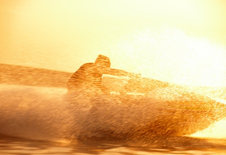 moto acuatica: hombre fuerte salta sobre el jetski por encima del agua al atardecer .silhouette spray. Foto de archivo