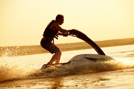 jet skier: strong man drive on the jetski above the water at sunset .silluet. spray Stock Photo