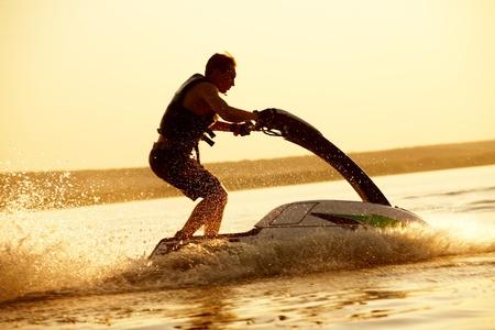 jet skier: strong man drive on the jetski above the water at sunset .silluet. spray Stock Photo