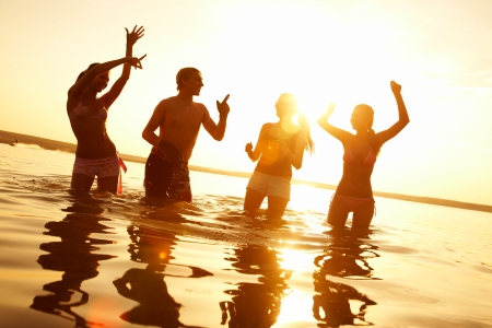 fun woman: group of happy young people dancing and spraying at the beach on  beautiful summer sunset Stock Photo