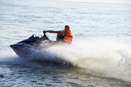 jet skier: Young couple riding her jet skis in the sea at sunset. Spray