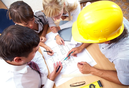 construction project: Meeting the team of engineers working on a construction project at the table. Up view Stock Photo