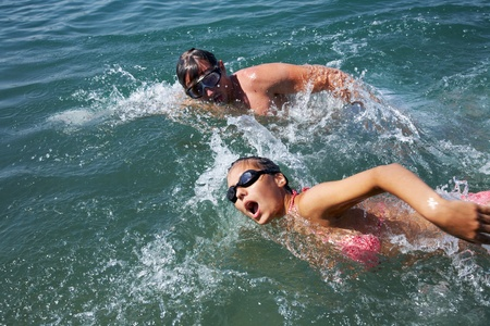 synchronously: Healthy lifestyle: man and woman are swimming together in open water