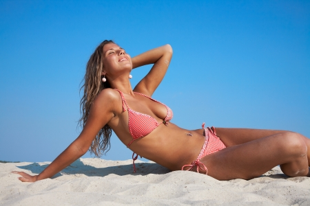 sunning: beautiful young woman in bikini lying and sunning on the beach under the bright sun