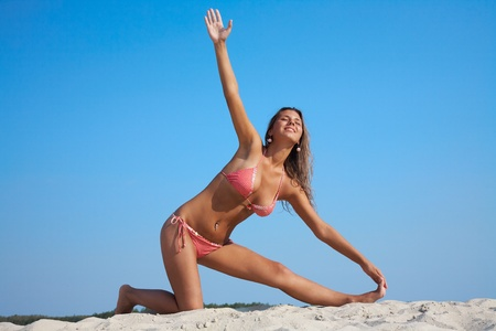 yogi: Mature sexy woman practicing yoga by the beach Stock Photo