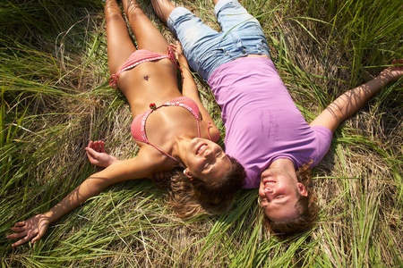 Young attractive couple relaxing in the grass photo