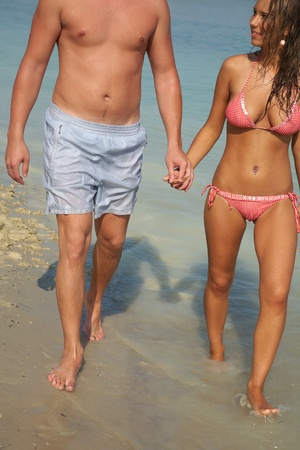 young couple in love walking through the water holding hands photo