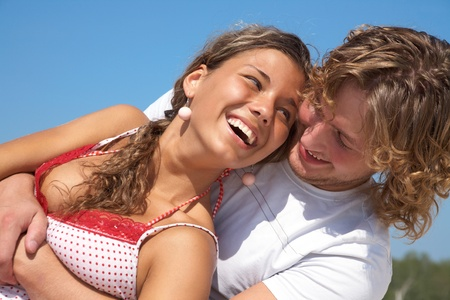 couple laughing: Young happy couple at the beach