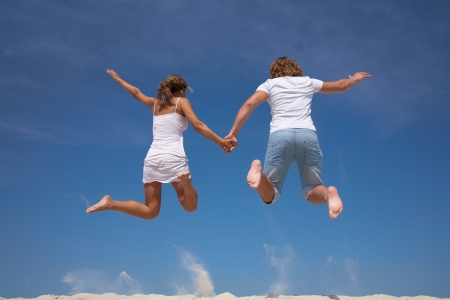 Photo of happy couple in jump with bright blue sky at background photo