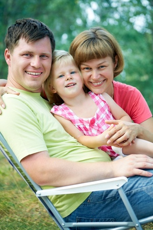 family lifestyle portrait of a mum and dad with their children sitting on folding chair  in the green  park photo