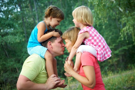mum and dad kiss  with their children  in the green  park Stock Photo - 10588643