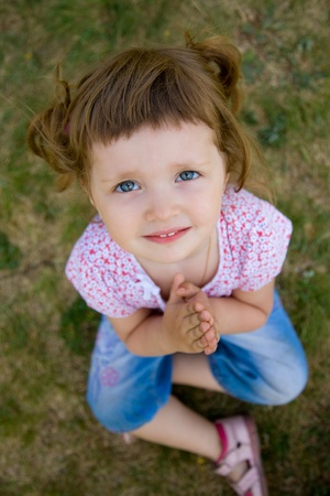 held:  pretty young girl praying with her hands held together Stock Photo