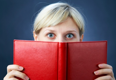 discovery: Young  Woman look in wide-eyed of the red book Stock Photo