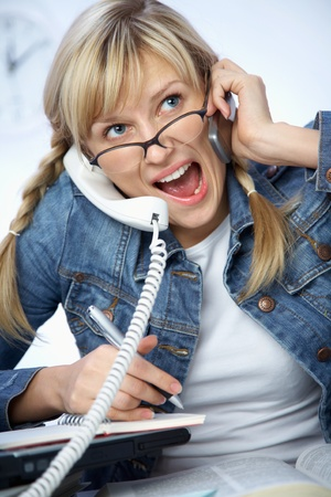 Hard-working young blonde crying to phone photo