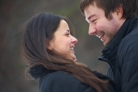 pair of beautiful young people hugging in the park in warm clothes photo