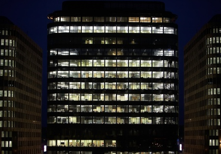 multi storey: Business skyscraper of glass and steel office lighting and working people within