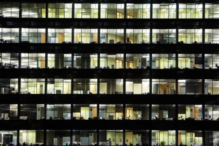 building business: window of the multi-storey building of glass and steel office lighting and working people within Stock Photo