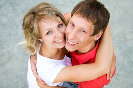 Portrait of a beautiful young couples are happily embracing at walk. Top view photo