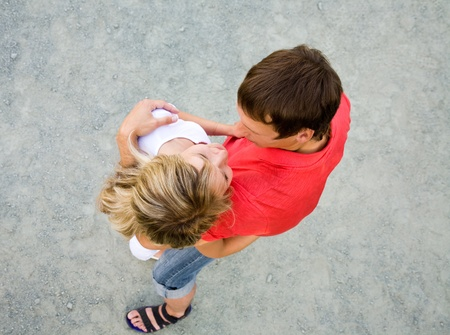 Portrait of a beautiful young couple are happily embracing at walk. Top view photo